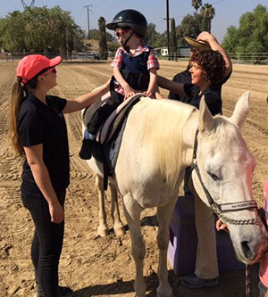 DPT students help a patient ride a horse