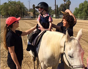DPT students help a patient ride a horse