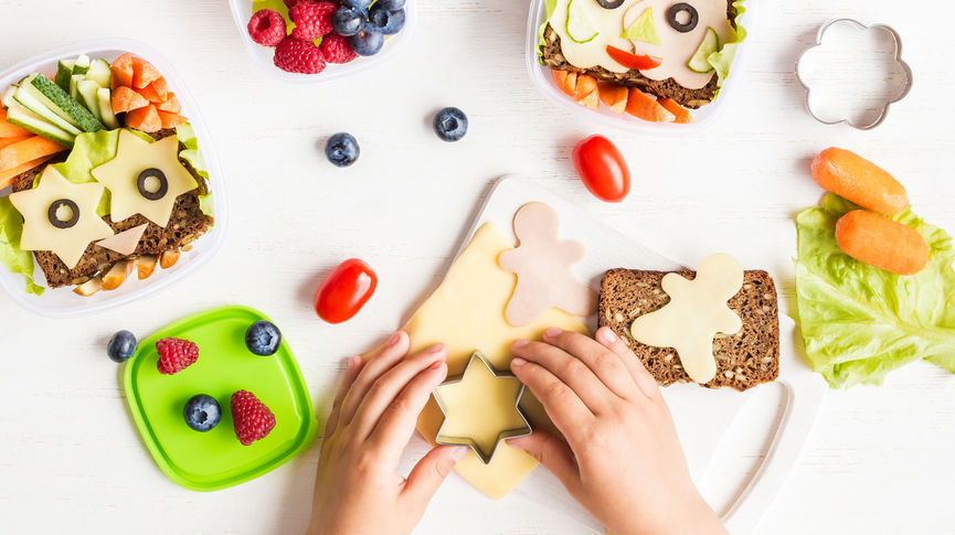parent making fun sandwiches with cheeses in different shapes