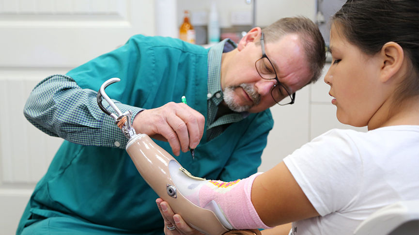doctor fitting a prosthetic arm to a female patient